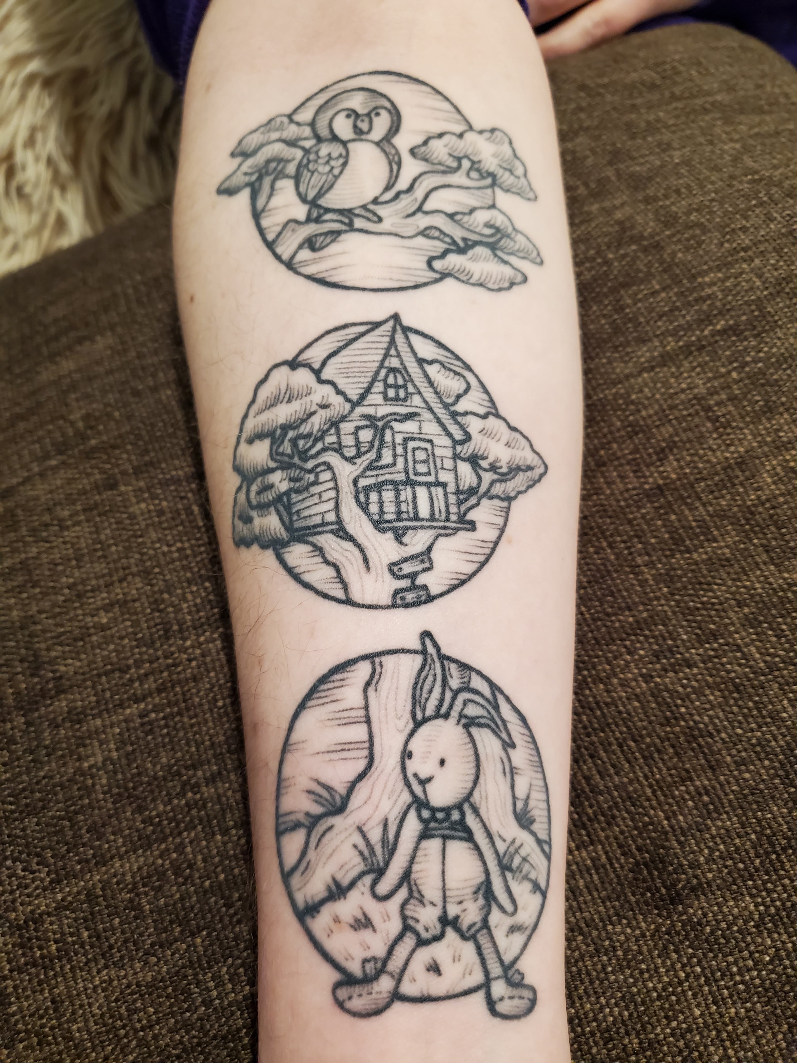 black line tattoo of an owl, a treehouse and a toy rabbit